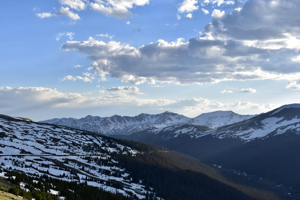 <p>A view from Trail Ridge Road, at over 10,000 feet, of the sun sinking low behind the mountains in Rocky Mountain National Park.&nbsp;</p>