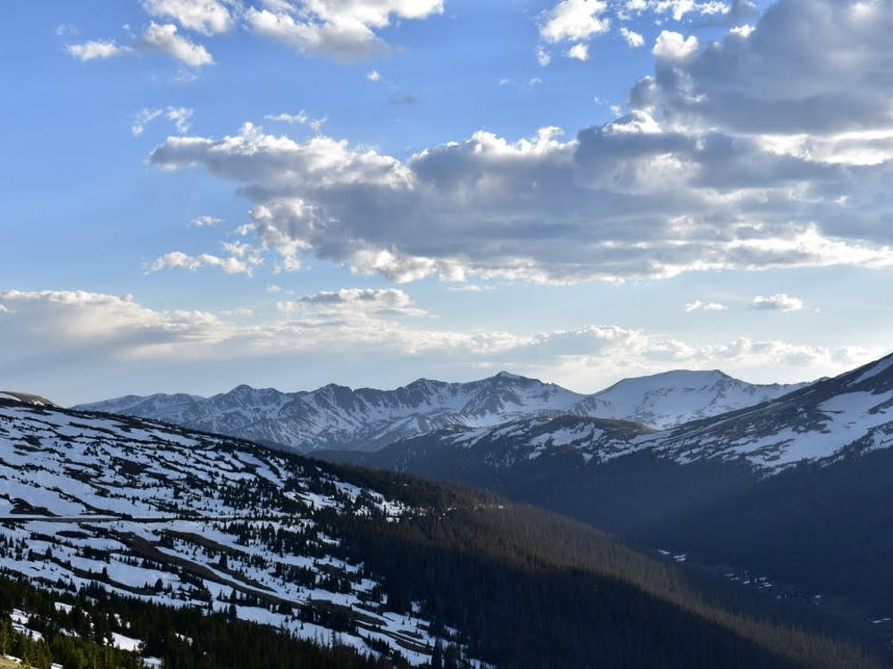 A view from Trail Ridge Road, at over 10,000 feet, of the sun sinking low behind the mountains in Rocky Mountain National Park.