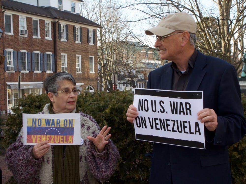 Retiree Alma Concepcion and Reverend Bob Moore, Executive Director of the Coalition for Peace Action, hold up anti-war signs. Photo taken by Claire Thornton / The Daily Princetonian