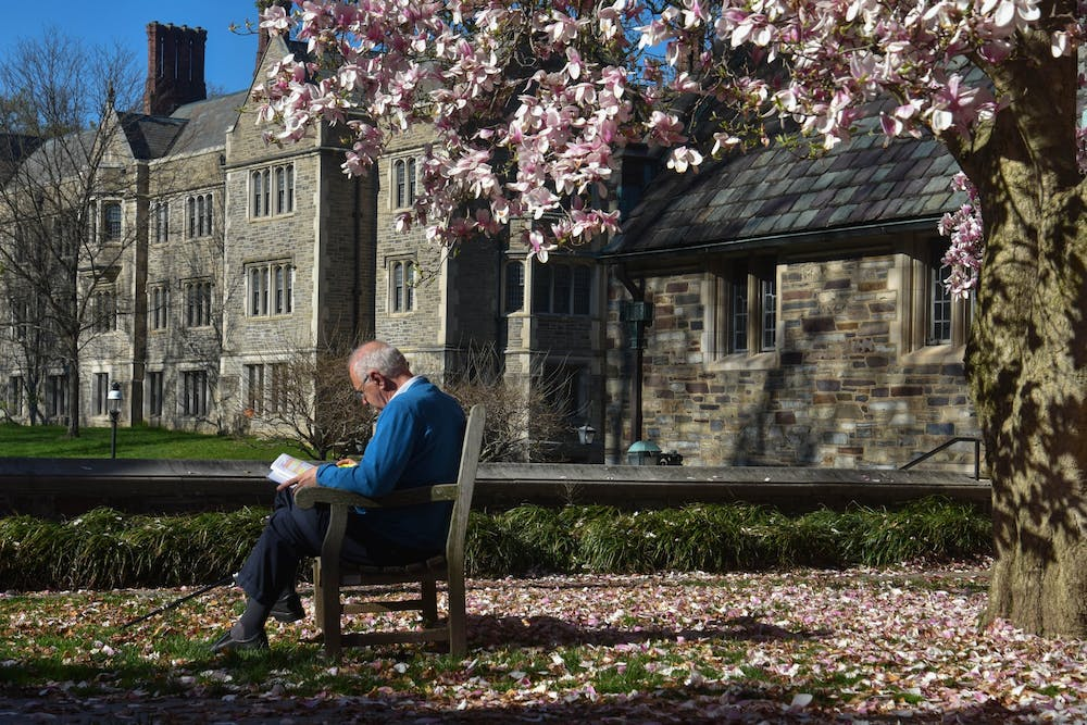 <h5>Princeton resident Ted Politis enjoys a warm afternoon, reading on a bench beneath a magnolia tree near Pyne Hall.</h5> <h6>Mark Dodici / The Daily Princetonian</h6>