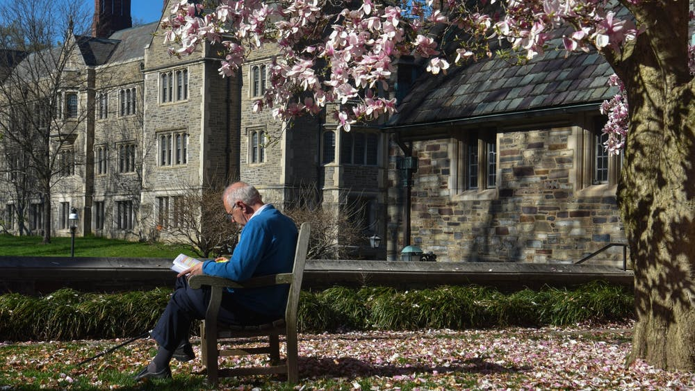 Princeton resident Ted Politis enjoys a warm afternoon, reading on a bench beneath a magnolia tree near Pyne Hall. Mark Dodici / The Daily Princetonian