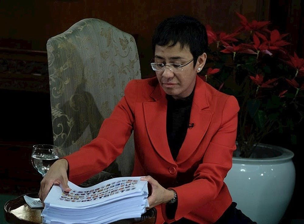 <p>Rappler CEO Maria Ressa '86 looks at the pile of documents containing names of government workers who are allegedly involved in the illegal drug trade in an interview with President Rodrigo Duterte in Malacañan Palace on December 29, 2016.</p> <p>Photo courtesy of Wikimedia Commons.</p>