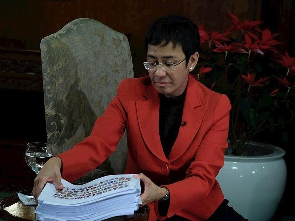Rappler CEO Maria Ressa '86 looks at the pile of documents containing names of government workers who are allegedly involved in the illegal drug trade in an interview with President Rodrigo Duterte in Malacañan Palace on December 29, 2016. Photo courtesy of Wikimedia Commons.