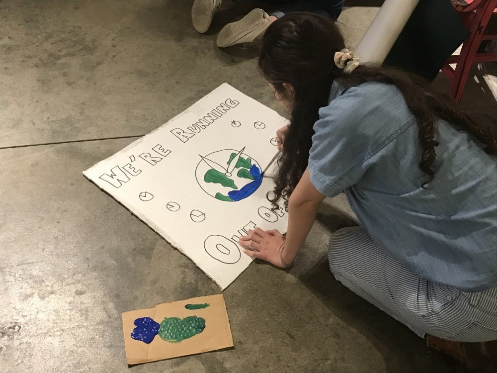 """<p>A student paints a """"We're Running Out of Time"""" poster ahead of the Princeton Climate Strike.</p> <h6>Photo Credit: Zachary Shevin / the Daily Princetonian</h6>"""