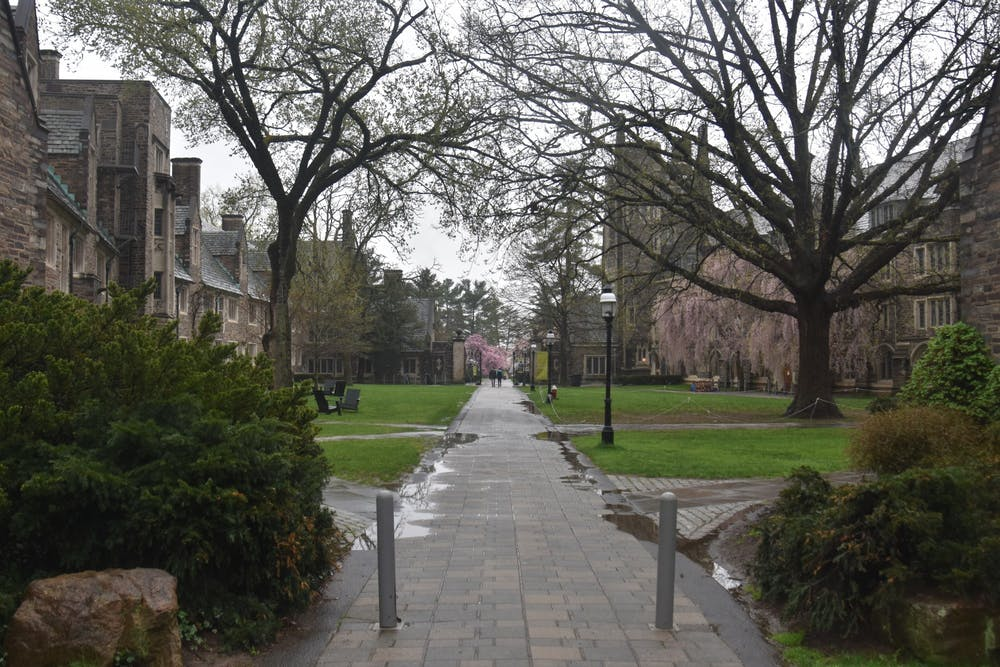 <h4>A solitary couple walk through Henry Courtyard on a rainy morning.</h4> <h5>Mark Dodici / The Daily Princetonian</h5>