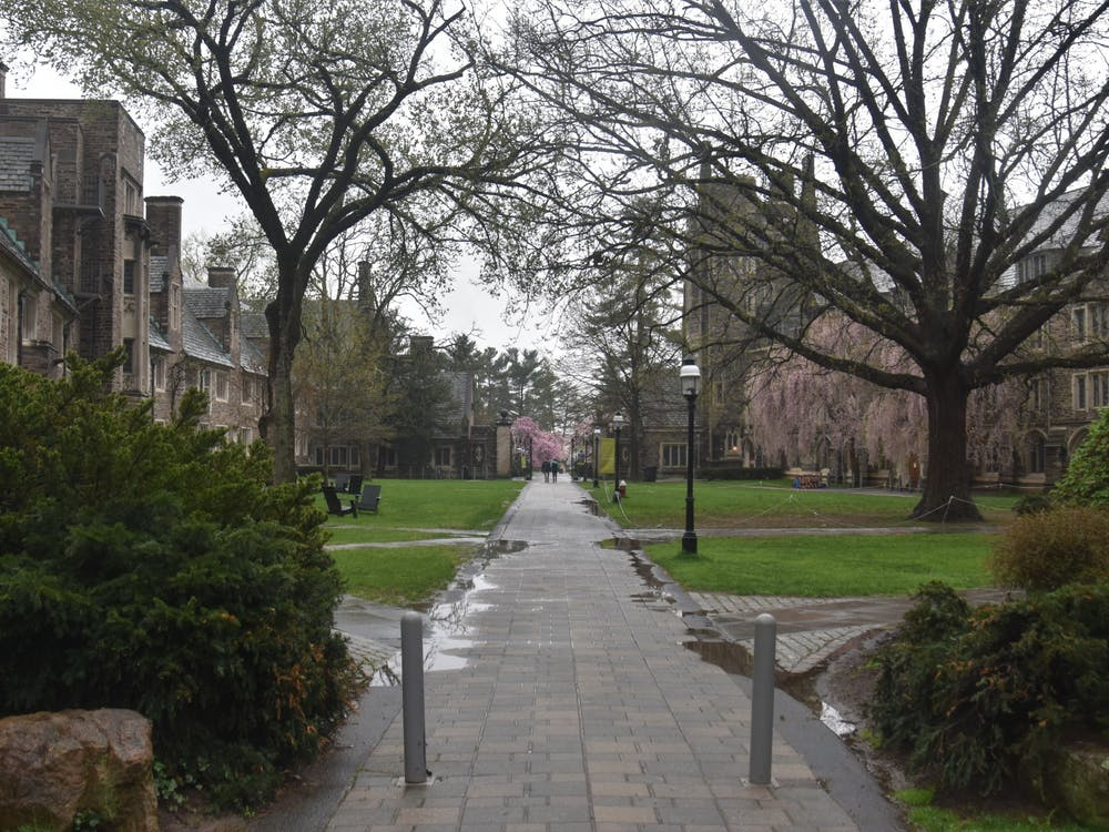 A solitary couple walk through Henry Courtyard on a rainy morning. Mark Dodici / The Daily Princetonian
