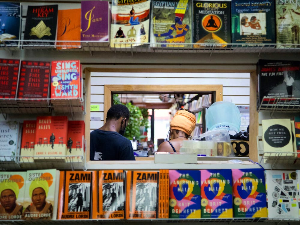 Patrice McKinney, co-owner of Source of Knowledge, and Nabate George, a Source of Knowledge employee, stand in the store framed by books, many of which are featured in Turn The Page's Black Liberation Literature Collections.  Courtesy of Maal Imani West
