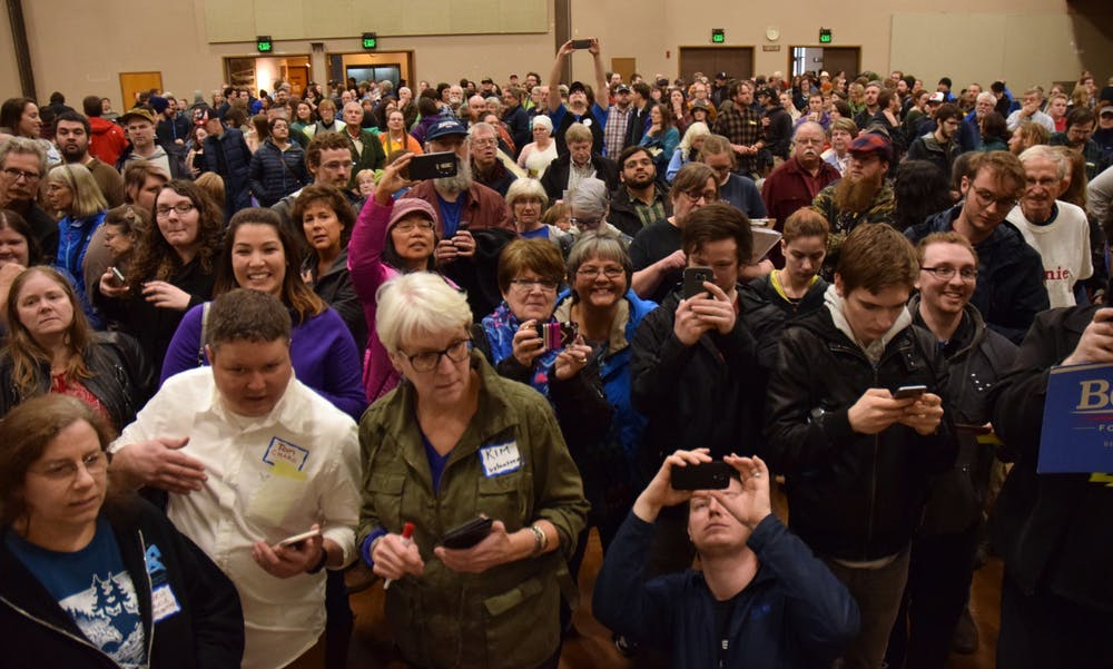 Kim Metcalfe and Tom Chard, bottom left, tally votes at the Juneau Democratic Caucus on Saturday, March 26, 2016 as voters hold up their cellphones to capture the results. (James Brooks photo)