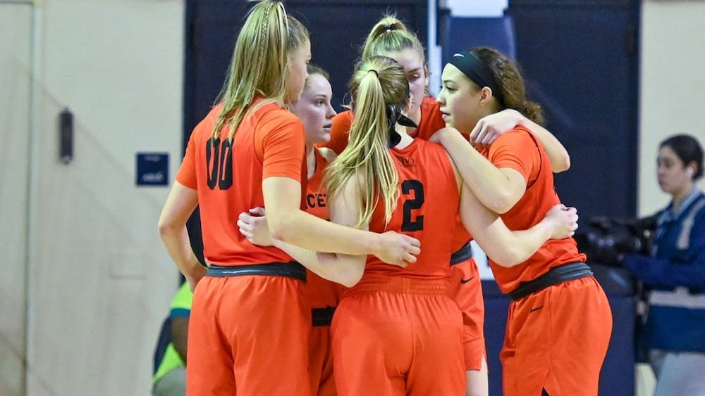 Caption: Princeton women's basketball players in a huddle during the game against Yale.  Credit: Patrick Tewey, goprincetontigers.com