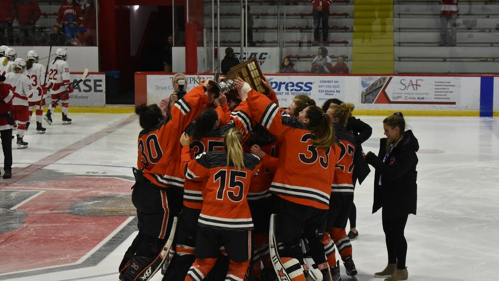 Caption: Women's ice hockey celebrates with the ECAC trophy after winning their first ECAC championship in program history.  Credit: Owen Tedford/The Daily Princetonian