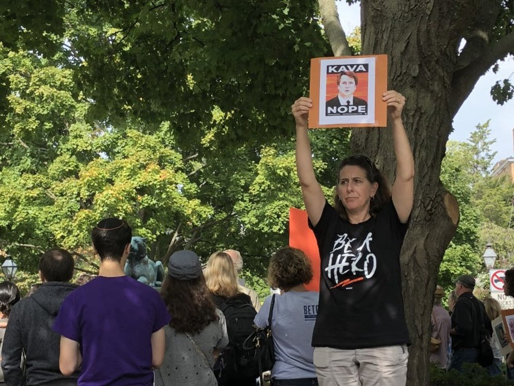 """One protester holds a sign up during the """"Emergency Rally"""" on Oct. 4 in Tiger Park."""