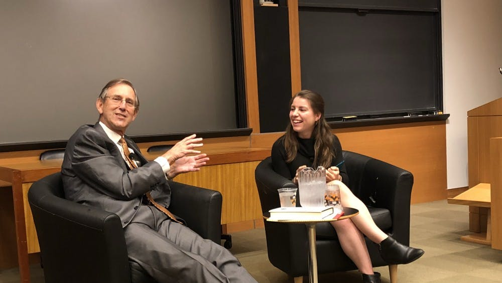 "Rick Barton, left, discusses his book ""Peace Works"" with MPA student Caitlin Quinn."