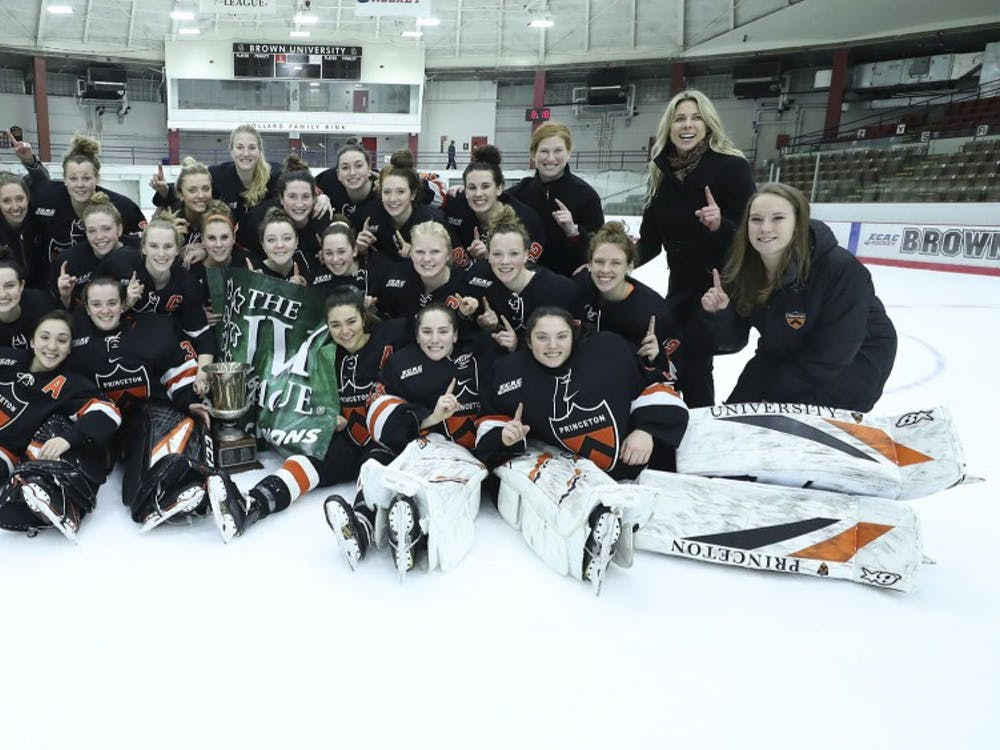 Women's hockey with their Ivy League championship trophy and banner after their win against Brown.