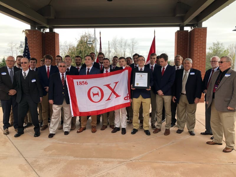 The brothers – past and present– of the Zeta Omicron chapter of Theta Chi fraternity hold their flag following the chapter's reinstallation on Nov. 17.