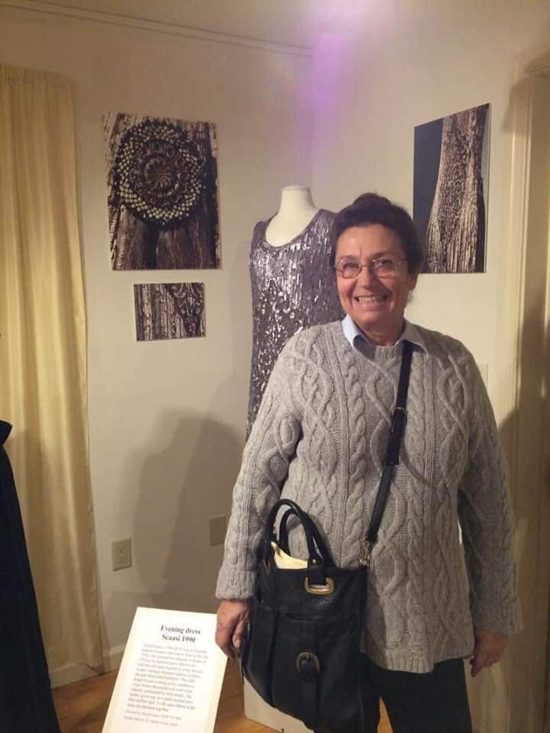 Agnes Ragone poses in front of an evening dress made in 1990 in the Fashion Archives and Museum.