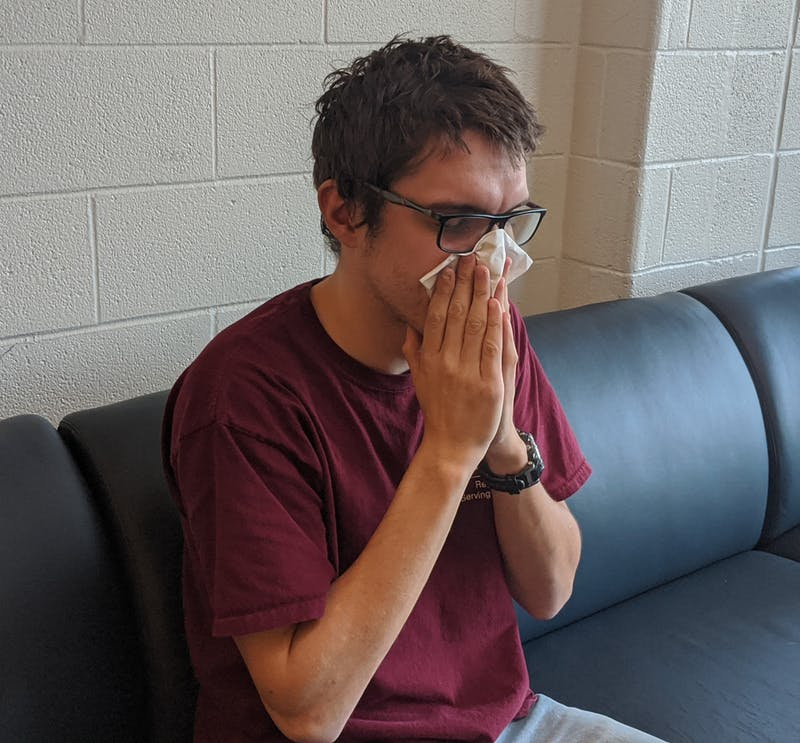 A student uses a tissue to blow his nose to prevent other students from also getting sick. Students should always use their elbow or a tissue when sneezing.