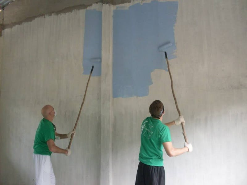 SU alumnus John Reed and student Zach Metz painting the inside of one of two new classrooms completed by the UCM team.
