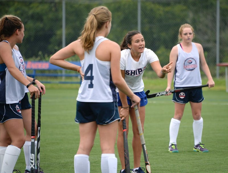 New field hockey head coach Tara Zollinger, right center, instructs SU field hockey players during practice.