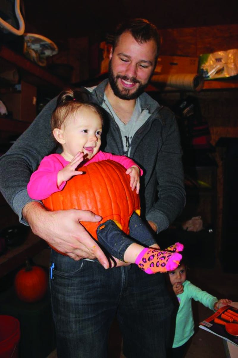 Matthew Ramsay holds his daughter inside of a pumpkin.