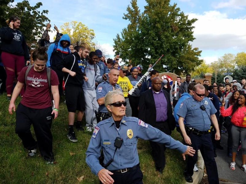 SU police officers escort a religious demonstrator to the edge of campus on Prince Street after more than 100 students showed up to challenge him. The man wore a yellow shirt and is seen holding a rolled up banner.