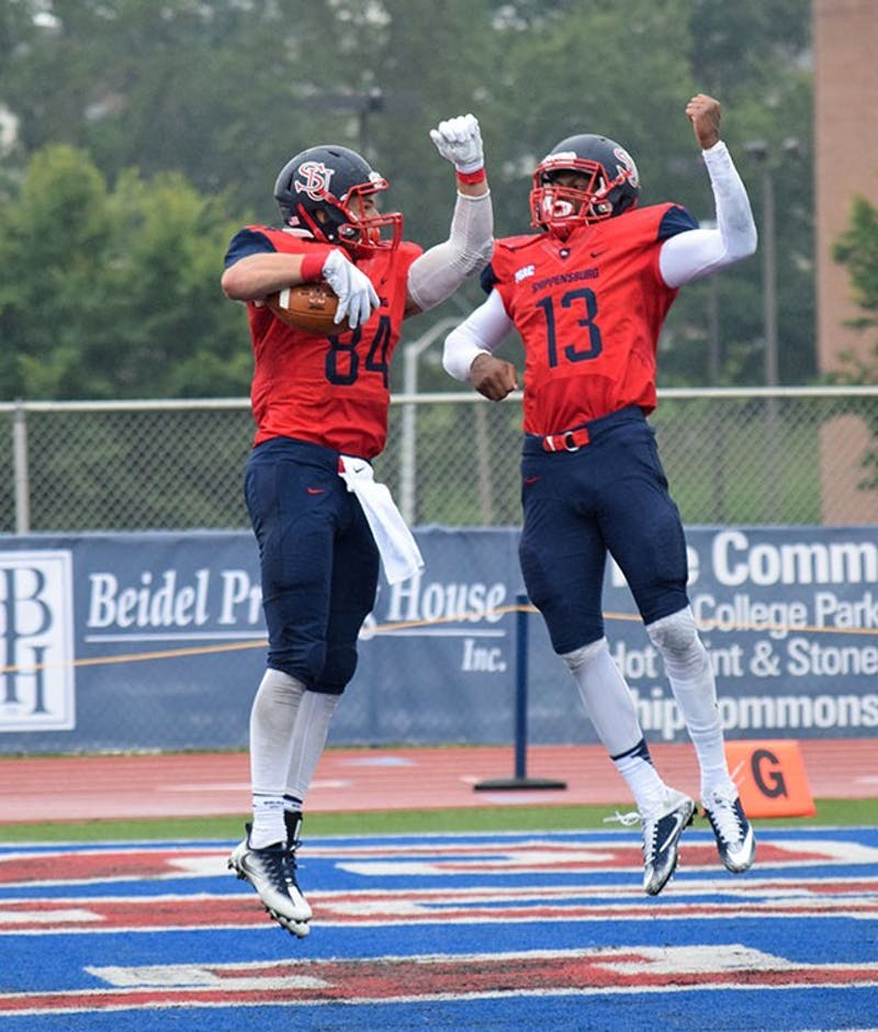 Shippensburg University's Kyle Haines, left, and Winston Eubanks, right, celebrate after Haines' 33-yard touchdown reception in the second quarter of SU's 41-7 thrashing of American International on Saturday.