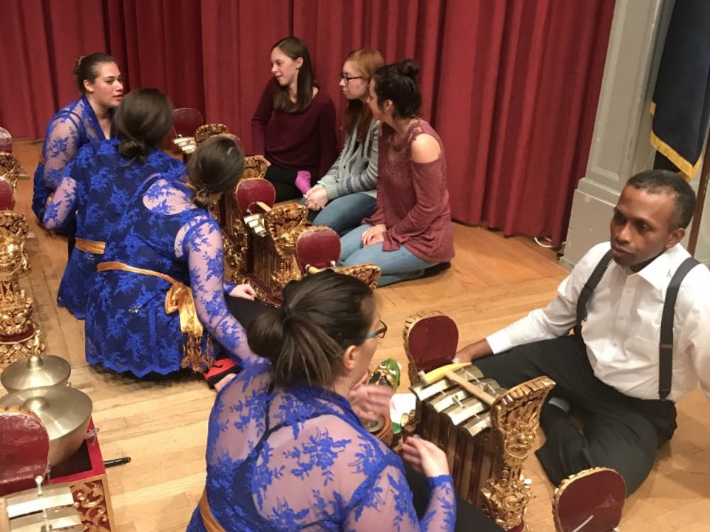 SU assistant professor of music Fred Dade sits with a member of the Gamelan Gita Semara to discuss gamelan music and its culture.