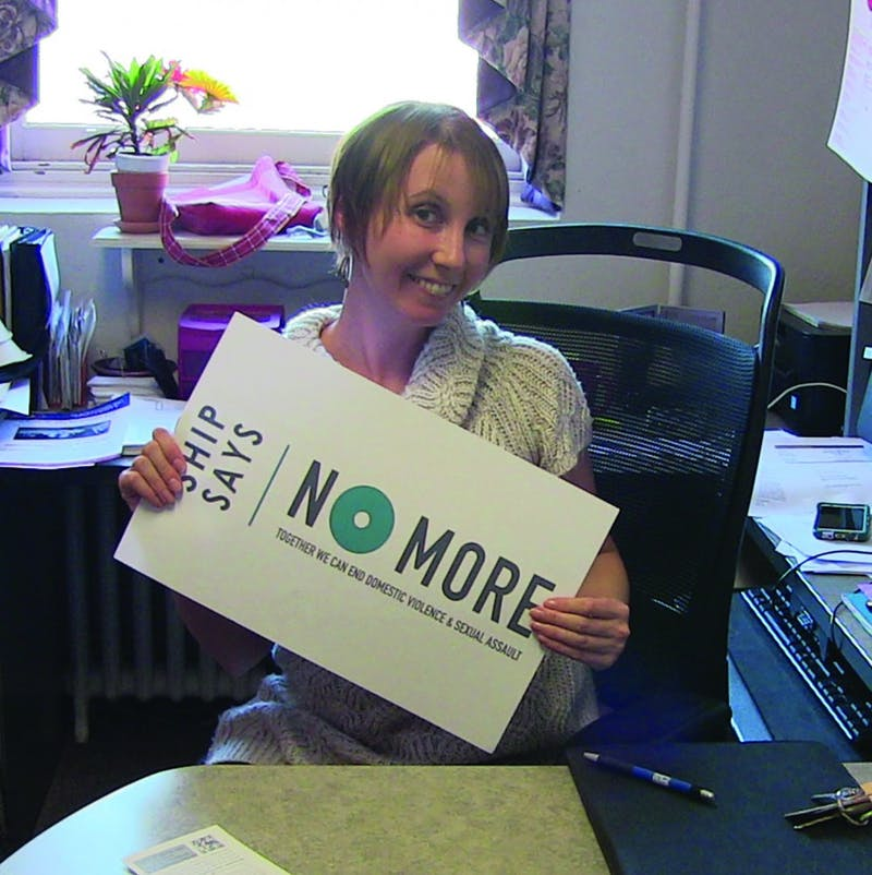Director of Women's Centers Stephanie Erdice models sign advocating intimate partner abuse awareness.
