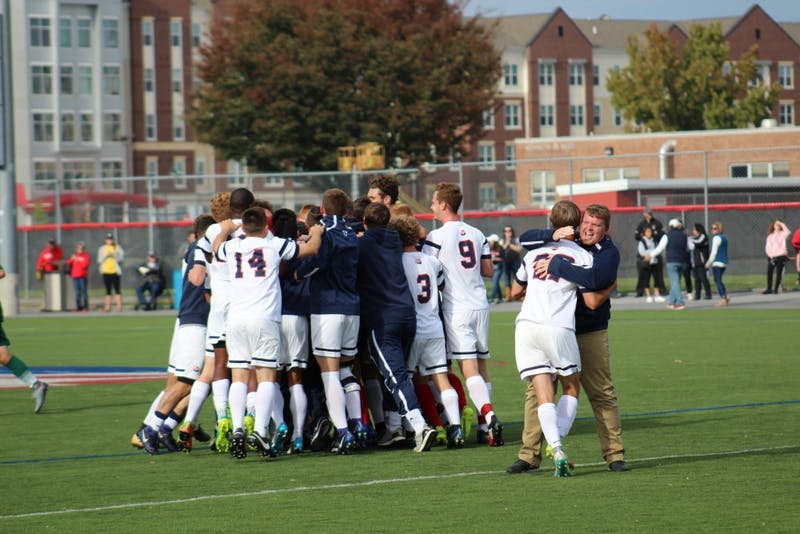 The team celebrates after a game-winning goal by Colin Marks against Slippery Rock University on Saturday to end the Raiders' season at 5–6 in the PSAC.