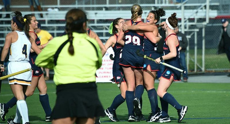 The field hockey team celebrates scoring one of its four goals in Sunday's playoff victory over Merrimack.