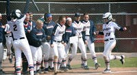 The team celebrates No. 29 Kendall Geis' home run against Holy Family.
