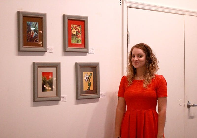 Tracie Leisher, a digital artist in Shippensburg stands next to her photography inspired by patterns of nature.