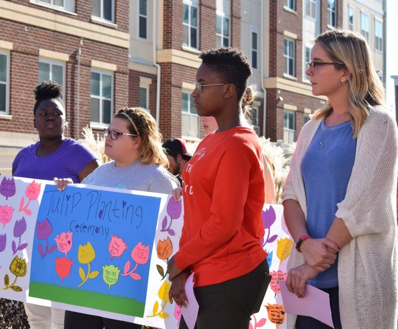 Students stand in remembrance of victims of domestic violence during the annual Tulip Planting Ceremony.