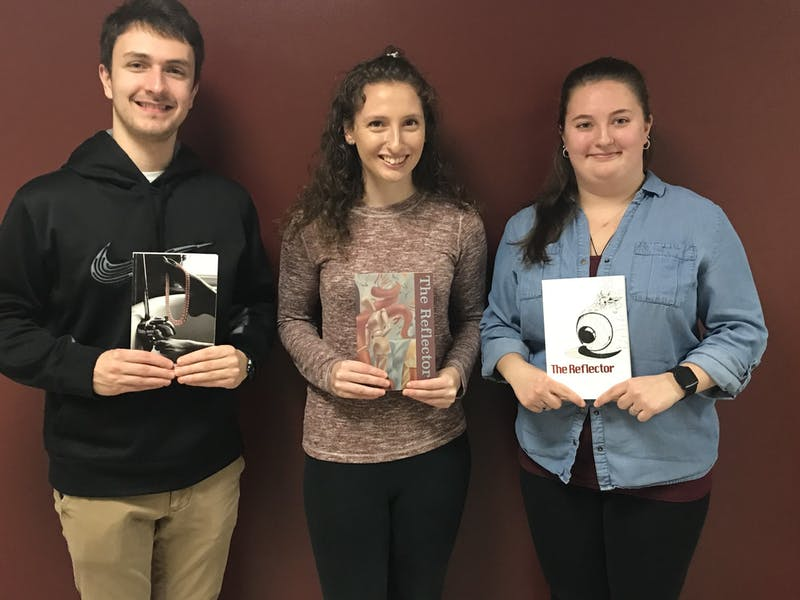 "(From left) Public Relations Chair Luke Hershey, Editor-in-Chief Anna D'Orazio and Associate Editor Angela Piper hold previous editions of ""The Reflector."""