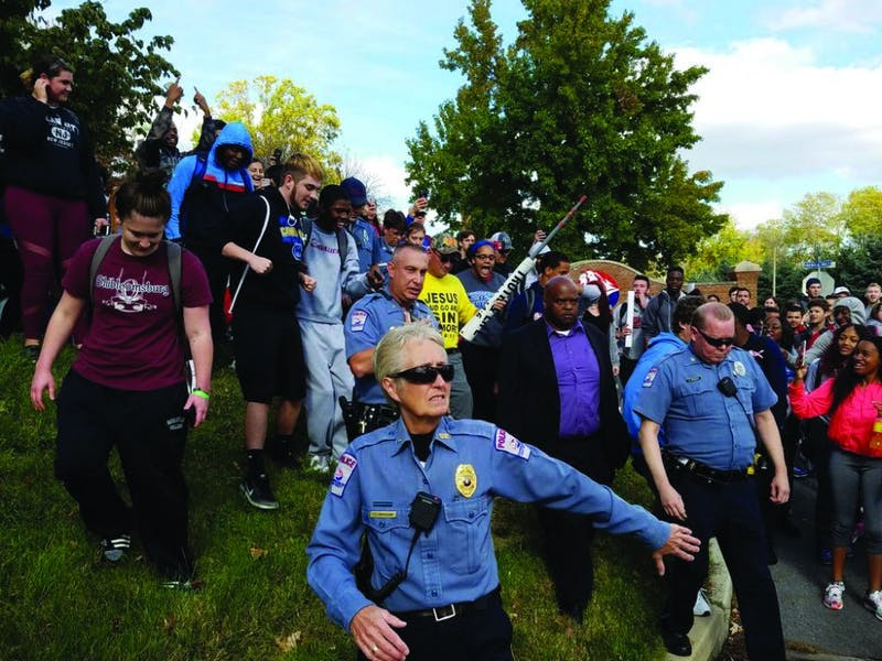 Police escort a religious demonstrator off of campus to the delight of the students who follow behind. The man agreed to be escorted off of campus after a large group of students showed up to protest his hateful message.