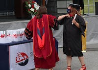 Instead of the usual hugs and handshakes, faculty and graduates shared elbow bumps.