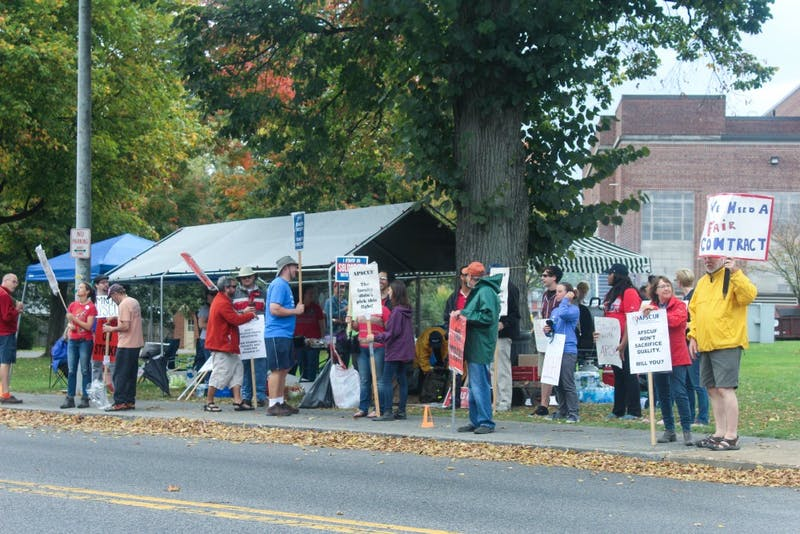 Faculty stand out in the rain on North Prince Street after hearing that Kenneth Mash was in meetings to end the strike.