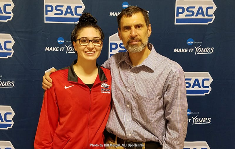 Shippensburg University's Stephanie O'Toole (left) and swimming coach Tim Verge (right) pose at the podium after O'Toole defended her title in the 200-yard IM at the 2018 PSAC Championships on Feb. 21.