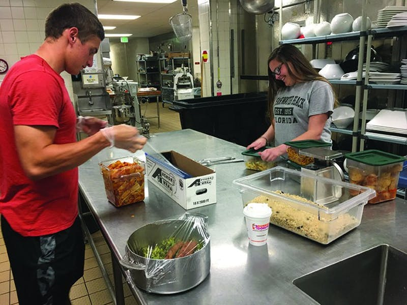 Students help package leftover food in Reisner Dining Hall to take to local organizations. The packaged food provides additional meals for people.