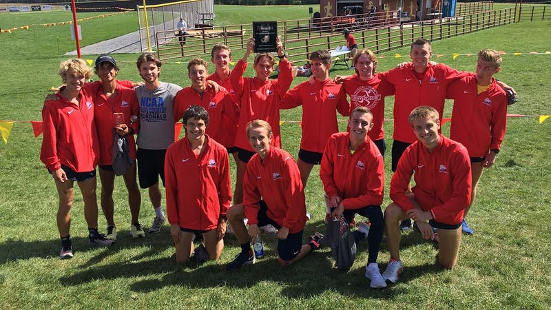 The men's cross country team celebrates with the winning plaque after taking home the title in the 4K race in Newville at Big Spring High School on Saturday.