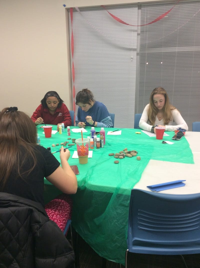 Students paint rocks to relieve anxiety and enjoy a night of tarot cards and music at the wellness event.