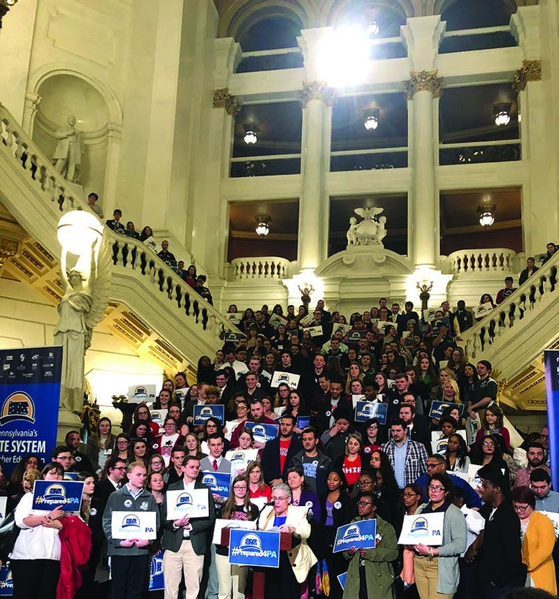 Students gather on the stairs in the Capitol building's rotunda while speakers including Interim Chancellor Karen M. Whitney and SU President Laurie Carter deliver speeches. Carter emphasized her experience at Clarion University and how it prepared her future and how she feels a connection to students at SU.