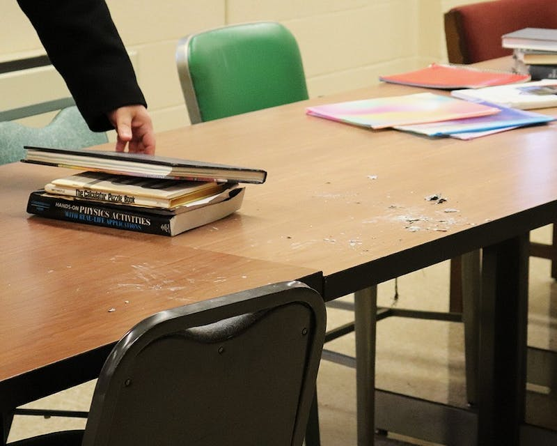 Shippensburg University Police Department Detective Karl Schucholz collects a set of books next to the pile of ashes as evidence in the case.