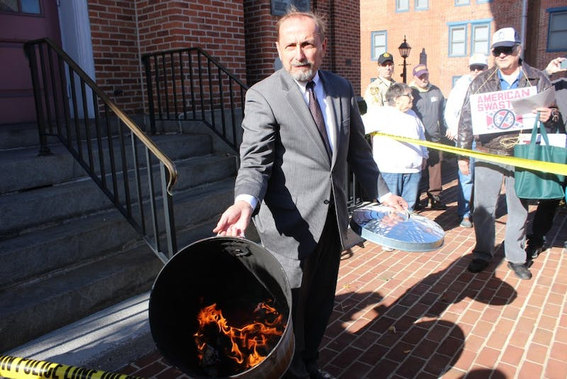 Gene Still displays a burning Confederate-Nazi flag to the crowd gathered outside of the Adams County Courthouse in Gettysburg on Nov. 17.