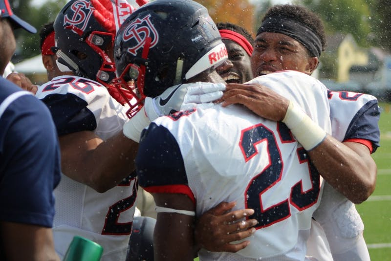 SU's Chavez Cheatham (No. 23) is greeted by teammates after returning a 54-yard interception for a touchdown Saturday against Clarion University.