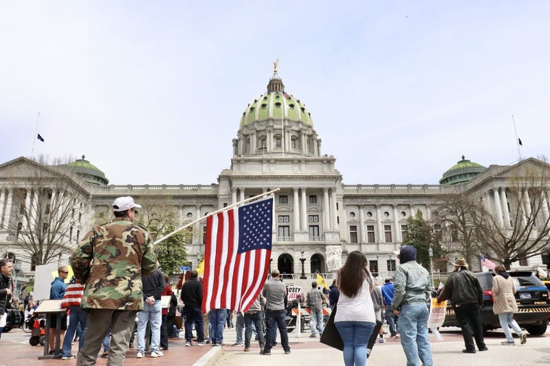 Protesters assembled in front of the Harrisburg Capitol Complex to protest restrictions imposed by Gov. Tom Wolf to mitigate the spread of the COVID-19 coronavirus.
