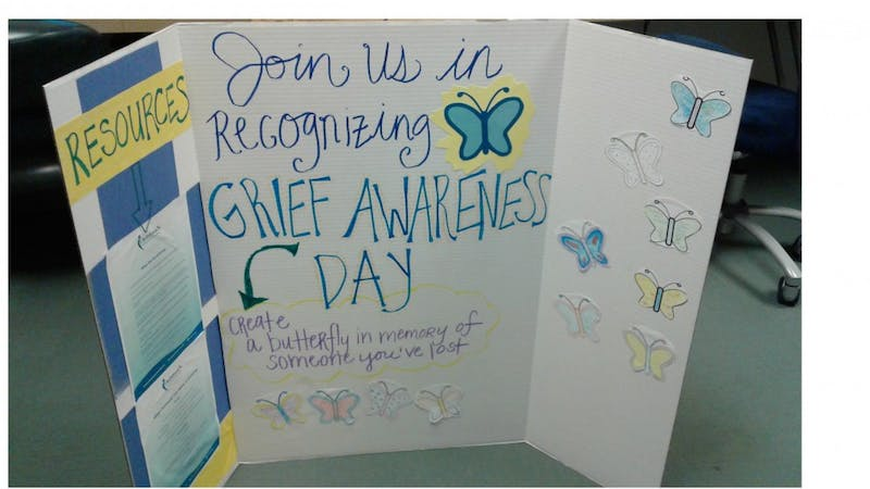 Graduate assistants from the counseling center invite students to create butterflies for grief awareness day.