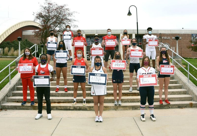 Several student-athetes hold up signs describing either themselves or the Shippensburg community. Each sign in the photo is different from every other.
