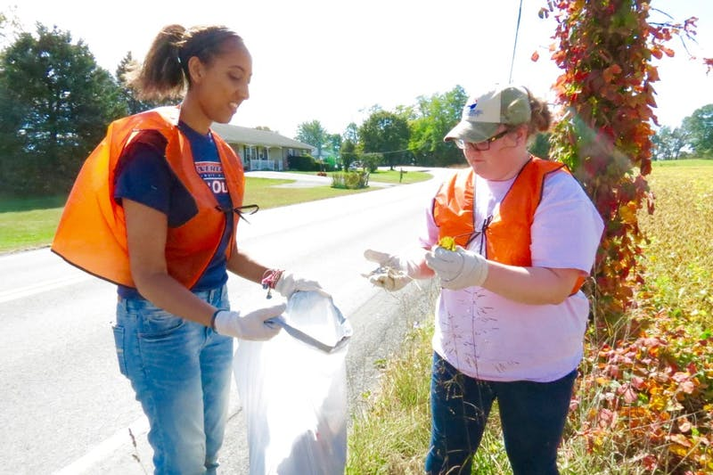 Abrihet Zegeye (left) holds a trash bad open for Katy Gentile to put in debris.