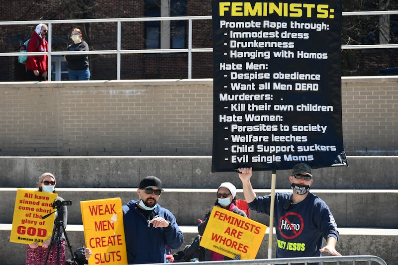 Pastor Aden Rusfeldt, right, and James Ross hold signs while preaching students outside of the Ceddia Union Building. They repeatedly spoke about the immoral behavior of women and what the role of women should be.