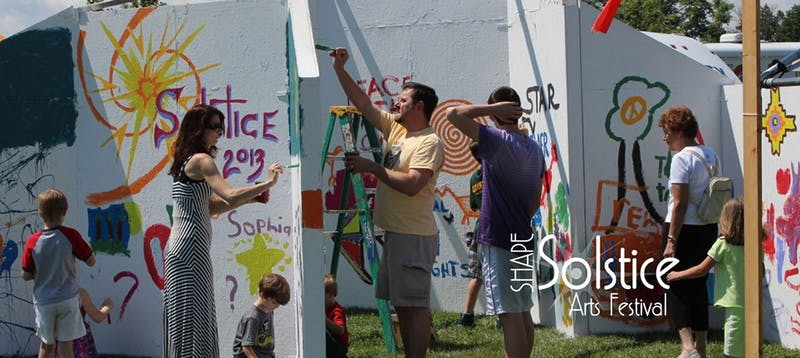 Festivalgoers paint on the Art Wall at a past SHAPE Summer Solstice Arts Festival.